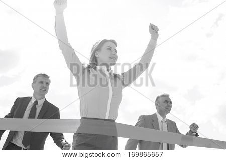 Low angle view of businesswoman crossing finishing line with colleagues in background