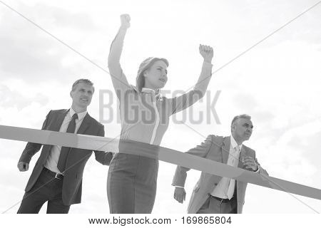 Businesswoman crossing finishing line with colleagues in background