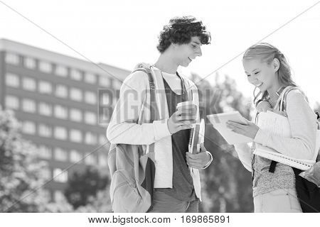Male and female students using digital tablet at college campus