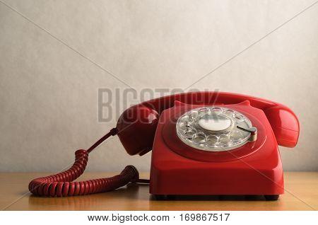 Retro Red Telephone On Light Wood Veneer Table