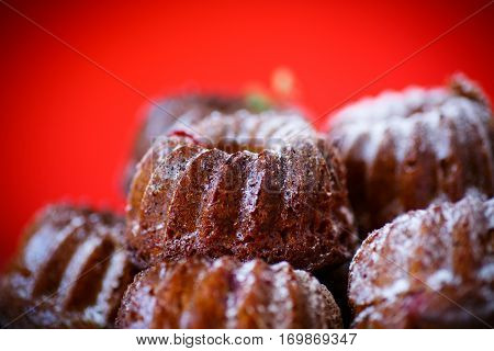 sweet honey muffins in powdered sugar on a red background