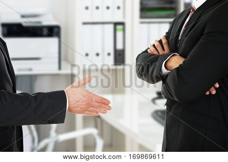 Person Offering Handshake To Businessman With Arm Crossed At Office