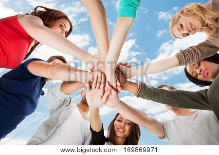 Low Angle View Of A Students Stacking Hands Against Sky