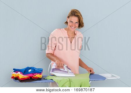 Smiling Woman Ironing Clothes Using Iron On Ironing Board At Home