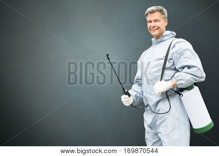 Pest Control Worker In Protective Workwear With Pesticides Sprayer Over Gray Background