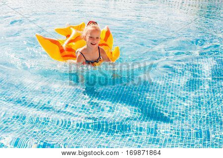 Portrait of cute happy little girl having fun in swimming pool, floating in blue refreshing water with inflatable ring, active summer vacation on the beach.