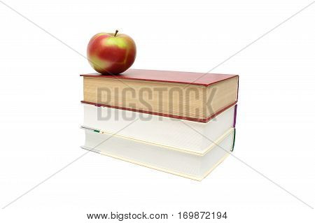 ripe apple lies on a pile of books on a white background. horizontal photo.