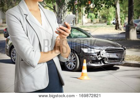Woman using phone after car accident, closeup. Traffic safety concept.