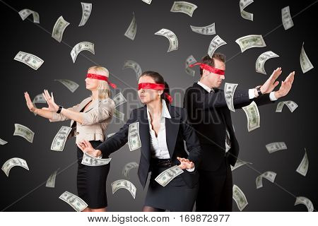 A Blindfolded Business People Standing In Money Rain On Gray Background
