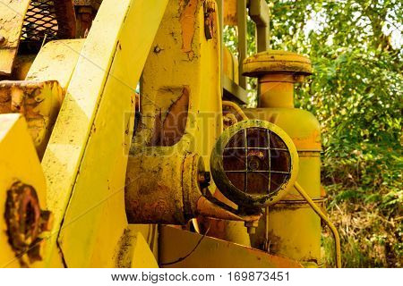 Old bulldozer forgotten in the mine. Big yellow rusted excavator.