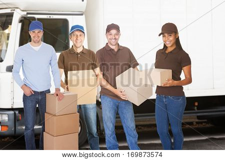 Group Of Delivery And Furniture Movers People Standing With Boxes Outside The Van