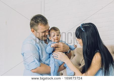 happy family consisting of mom and dad's baby boy. happy family relationships. father holding the baby in his arms. child flies