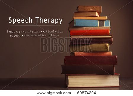 Stack of books on table. Text SPEECH THERAPY on background
