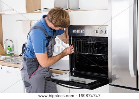 Repairman With Screwdriver Fixing Oven In Kitchen