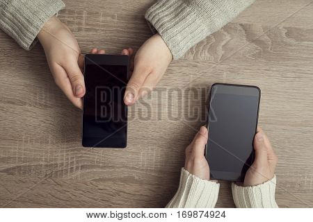 Top view of two people's hands holding smart phones and surfing the net. Selective focus