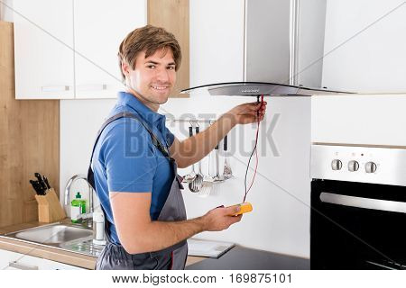 Young Male Checking Kitchen Extractor Filter With Multimeter In Kitchen Room