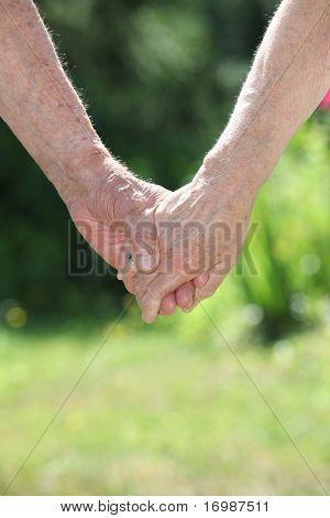 Closeup of elderly couple holding hands