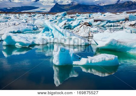 Drift ice Ice Lagoon - Jokulsarlon. Gorgeous morning light in the Ice Lagoon. Icebergs and ice floes are reflected in the smooth water surface. The concept of extreme northern tourism