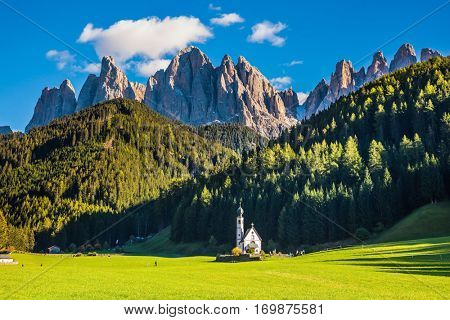 The famous symbol of the valley Val di Funes - church of Santa Maddalena. Rocky peaks and forested mountains surrounded by green Alpine meadows. Dolomites, Tirol. Sunny warm autumn day