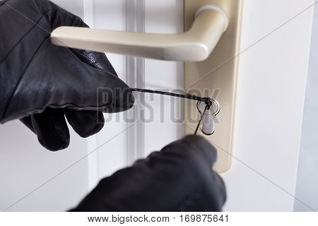 Close-up Of A Burglar With Gloves Picking Lock