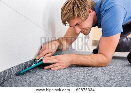 Close-up Of Happy Young Craftsman Cutting Carpet With Cutter At Home