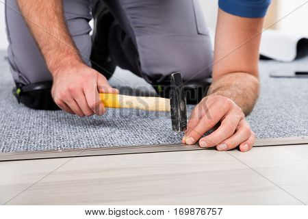 Close-up Of Person's Hand Using Hammer And Nail For Fixing Carpet