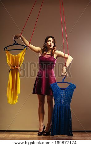 Shopaholic fashion addiction concept. Addicted to shopping woman girl marionette puppet with clothes on string buying disorder.