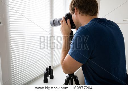 Private Detective Holding Camera Photographing Through Blinds At Home