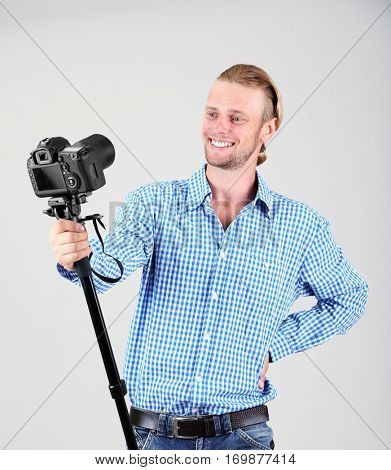 Handsome photographer with camera on monopod, on gray background