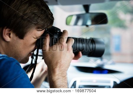 Man Sitting Inside Car Photographing With SLR Camera