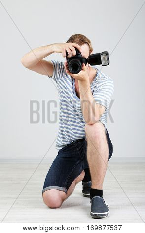Handsome photographer with camera, on gray background