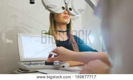 Woman doing eye test with optometrist in medical center, close up