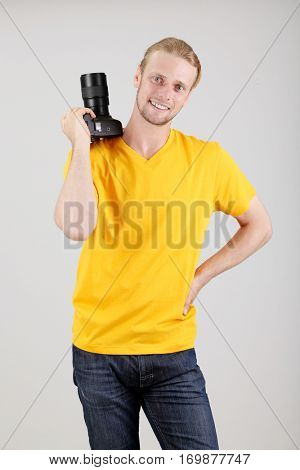 Handsome photographer with camera,on gray background