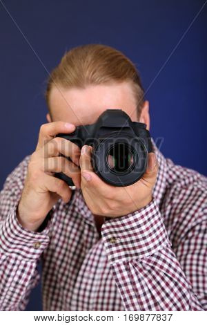 Handsome photographer with camera,on dark color background