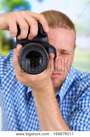 Handsome photographer with camera,on bright background