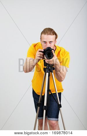 Handsome photographer with camera on tripod,on gray background
