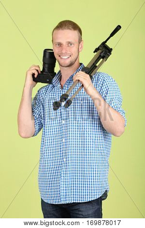 Handsome photographer with camera and tripod, on green background