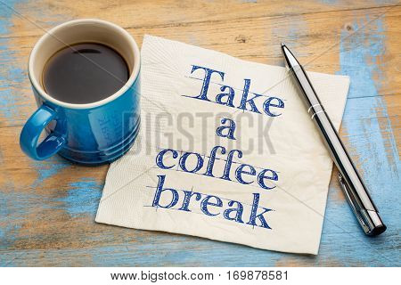 Take a coffee break handwriting on a napkin with a stoneware cup