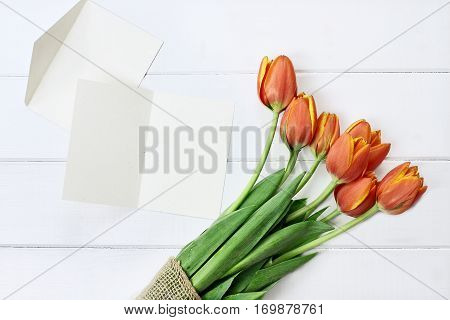 Overhead shot of a blank card and a bouquet of tulips over a white wood table top. Flat lay top view style.