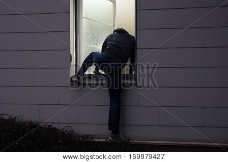 Rear View Of A Burglar Entering In A House Through A Window