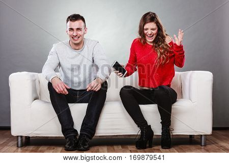 Angry furious wife shouting at husband showing text messages from lover mistress on his mobile phone. Outraged girlfriend find out about boyfriend affair romance betrayal. Cheating man laughing. poster