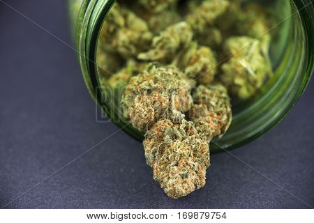 Detail of cannabis bud (crimson strain) on green glass jar - medical marijuana concept