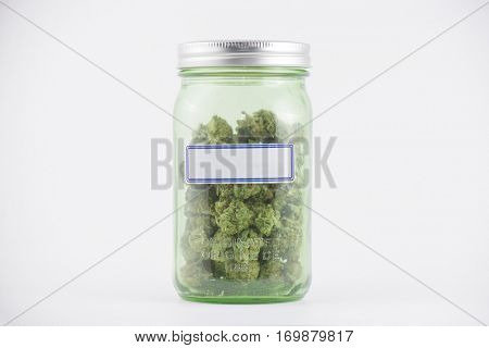 Detail of cannabis buds on green glass jar with blank label isolated on white - medical marijuana concept