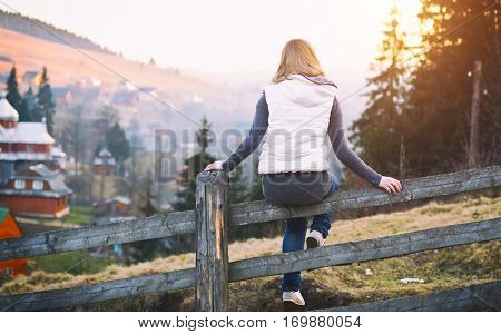 A young girl is sitting on the fence in the mountains