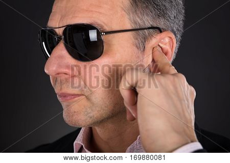 Close-up Of A Male Security Guard Listening To Earpiece On Gray Background