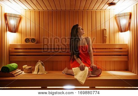 woman relaxes in a modern, beautiful sauna after Exercise
