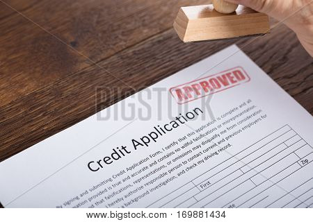 High Angle View Of A Person Holding Stamp On Approved Credit Application Form