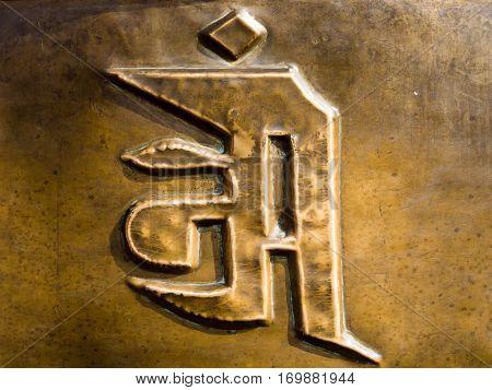 Sanskrit symbol on bronze colored metal surface