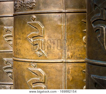 Bronze praying drums with Sanskrit symbols in a Buddhist temple