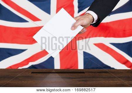 Businessperson Hand Putting Vote Into Ballot Box In Front Of United Kingdom Flag